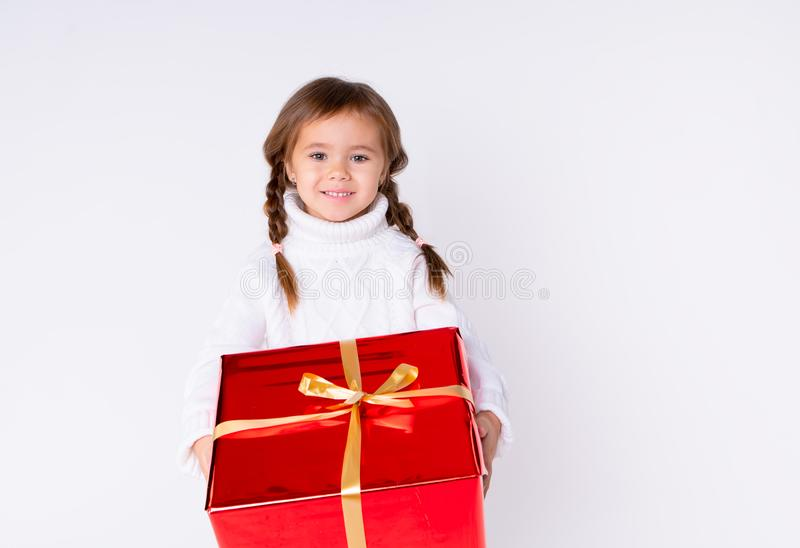 Little cute girl in knitted white sweater holding a present in studio. Concept Christmas, New Year, Birthday stock image