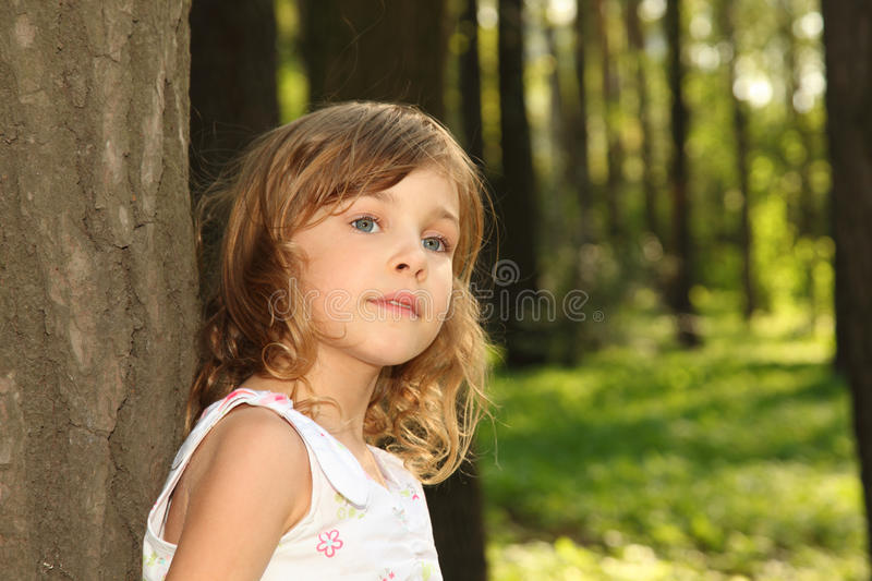 Little cute girl leaning against tree royalty free stock images