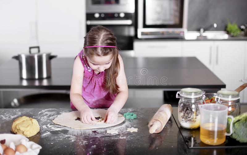 Little cute girl is learning how to make cake, in kitchen, Family concept stock images