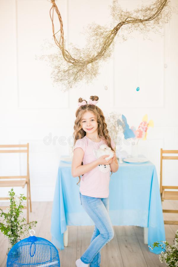 Little cute girl with long curly hair with little bunnies and Easter decor at home at the  table. stock photo