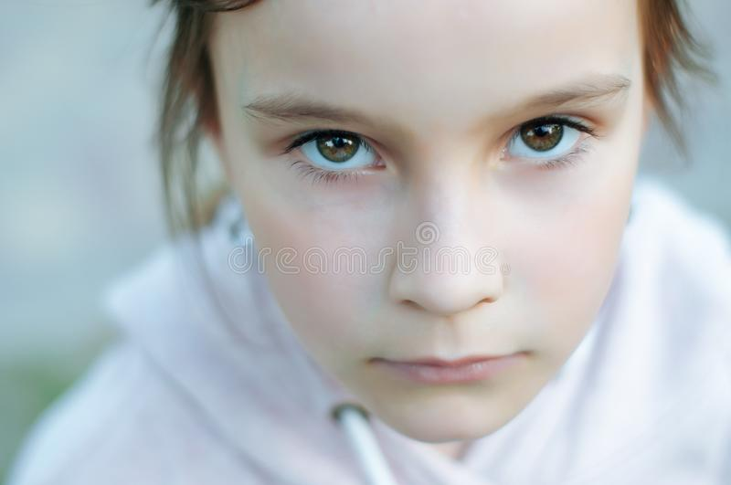 A little cute girl with long hair is sitting in a park seriously sad royalty free stock images