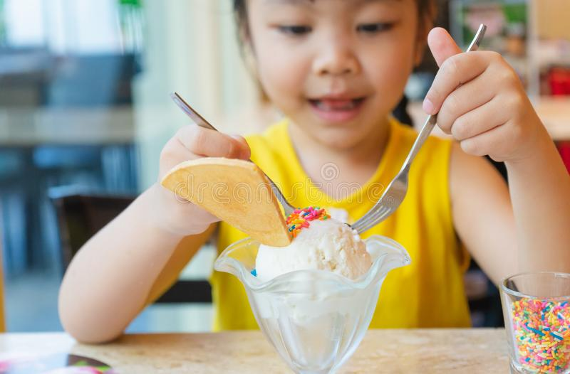 Little cute girl looking at coconut icecream with Rainbow Suga. R Cookies topped .selective focus on icecream royalty free stock image