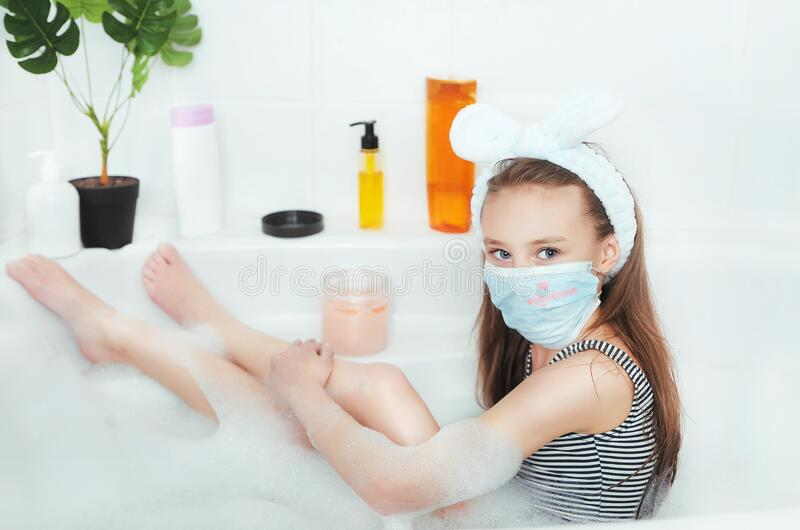 Little cute girl in mask makes scrubbing at home spa in the bathroom. Quarantine concept. Stay home royalty free stock photo