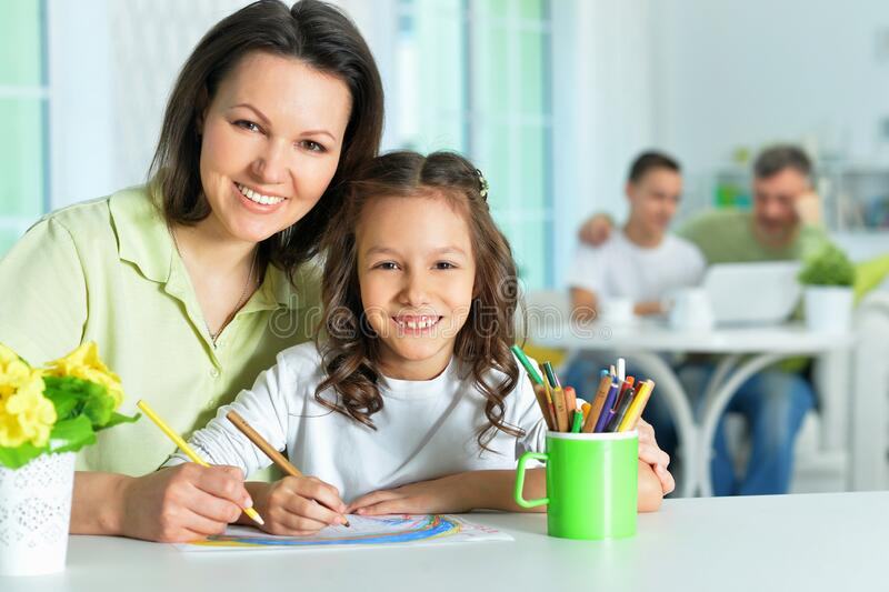 Portrait of little cute girl with mother drawing stock images