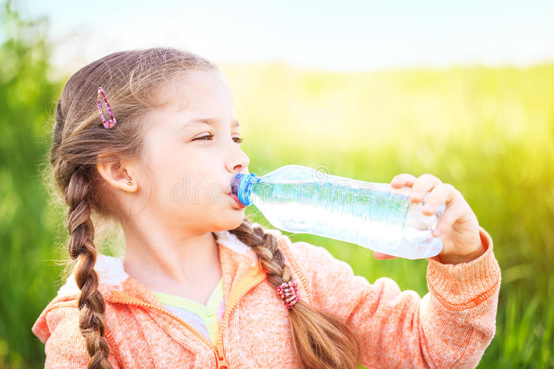 Little cute girl on the nature drinks water stock image