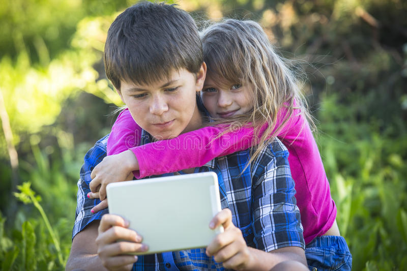 Little cute girl with an older brother holding the tablet stock image