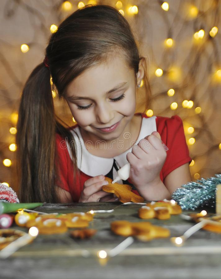 Free Little Cute Girl Paints Traditional Gingerbread Man. Stock Images - 168070694