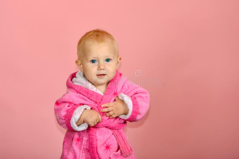 Little cute girl in a pink bathrobe on a pink background.  royalty free stock photos