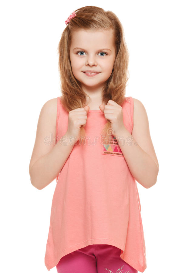 Little cute girl in a pink shirt holds hands hair, isolated on white background.  royalty free stock images