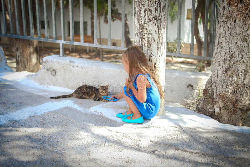 Little cute girl play with a cat on the streets of royalty free stock photography