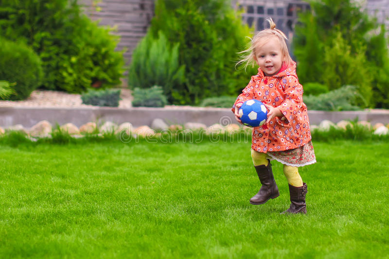 Little cute girl playing ball in the yard royalty free stock photo