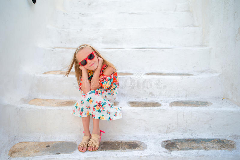 Little cute girl portrait outdoors in old greek village. Kid at street of typical greek traditional village with white. Girl in white dresses having fun outdoors royalty free stock photography