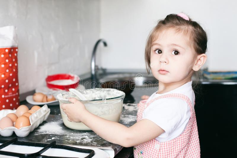 A little cute girl preparing the dough in the kitchen at home stock photography