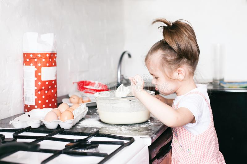 A little cute girl preparing the dough in the kitchen at home stock image