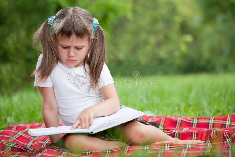 Little cute girl preschooler with book in park stock image