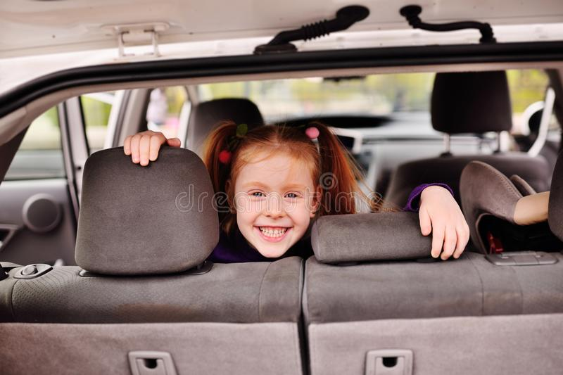 Little cute girl with red hair smiling at the background of the car interior stock photography