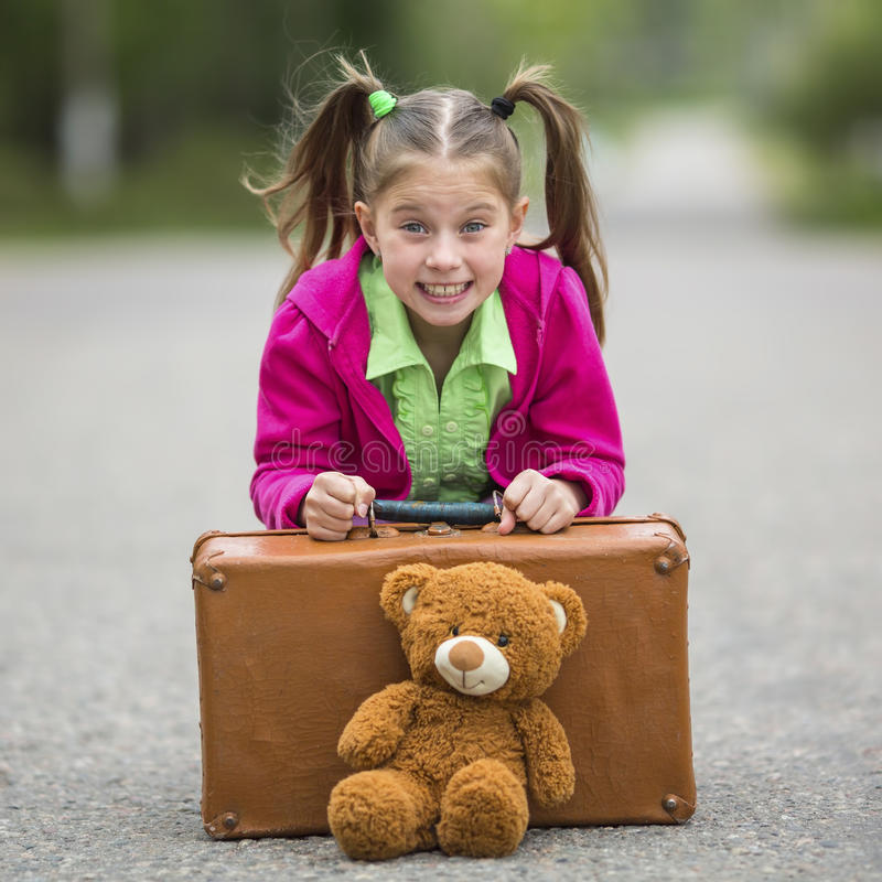 Little cute girl on the road with a suitcase. And a Teddy bear stock photo
