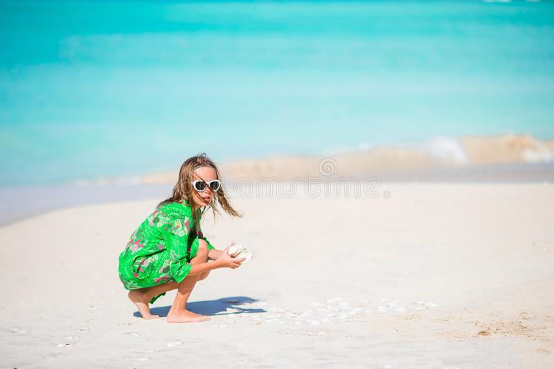 Little cute girl with seashell in hands at tropical beach. Adorable little girl playing with seashells on beach stock image