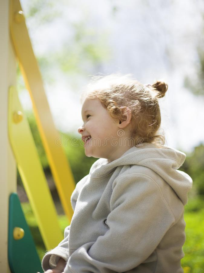 Little cute girl sits on a children slide and basks in the warm summer sun royalty free stock images