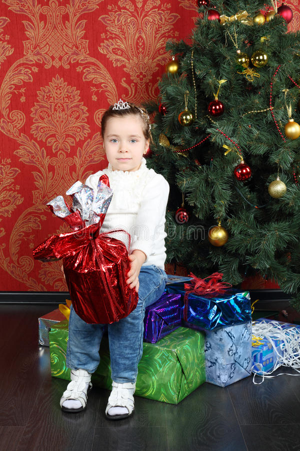 Little cute girl sits on gift on floor near Christmas tree. And holds gift at home royalty free stock images