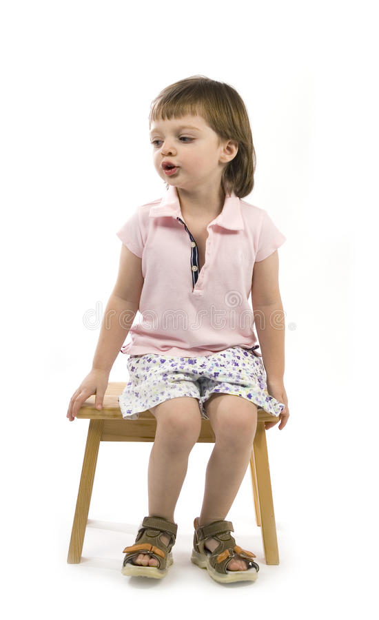 Little cute girl sitting on a chair