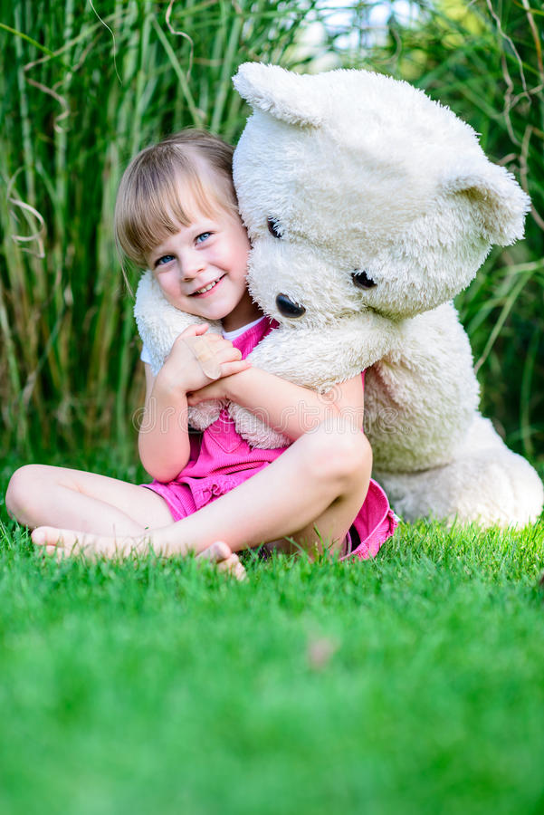 Cute girl with a teddy bear royalty free stock photography