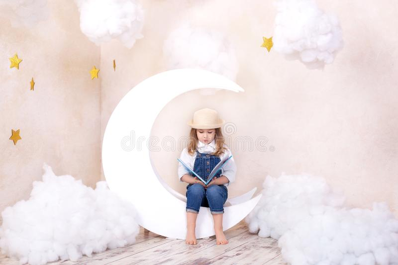 Little cute girl sitting on the moon with clouds and stars with a book in her hands and reading. The girl is learning to read. Rea stock photography