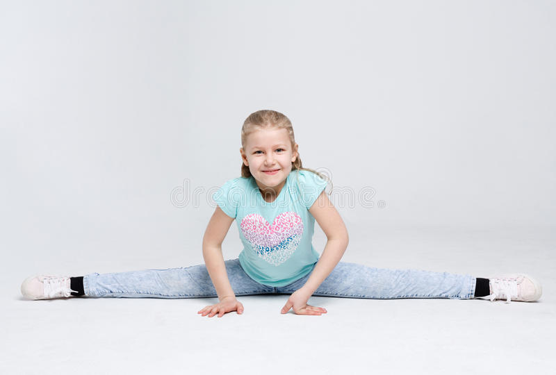 Little cute girl sitting in the splits on white studio background royalty free stock photography