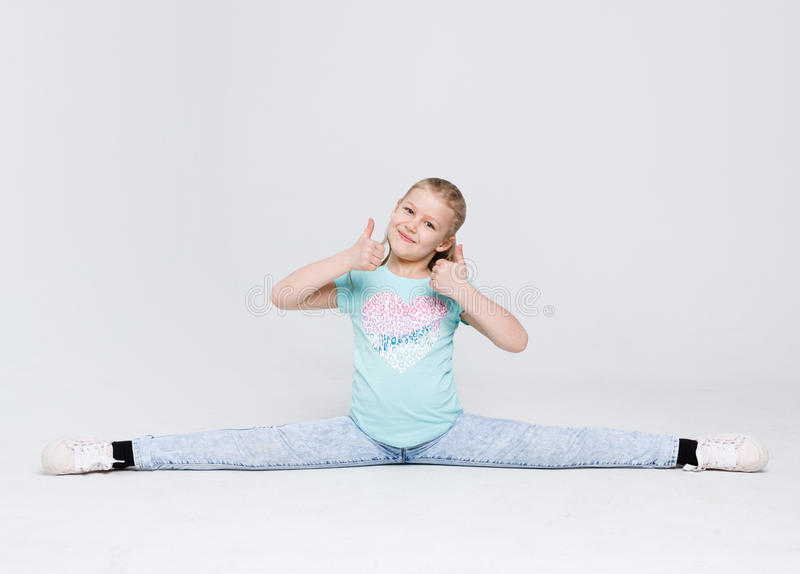 Little cute girl sitting in the splits on white studio background stock image
