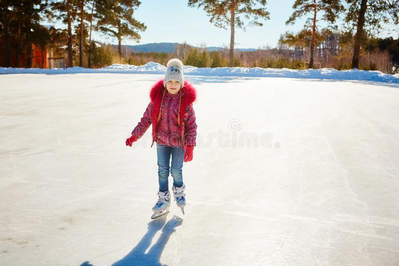 Little cute girl skating on the rink in the highlands.  royalty free stock photos