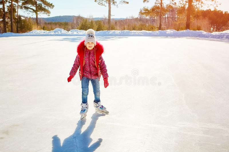 Little cute girl skating on the rink in the highlands.  stock photo