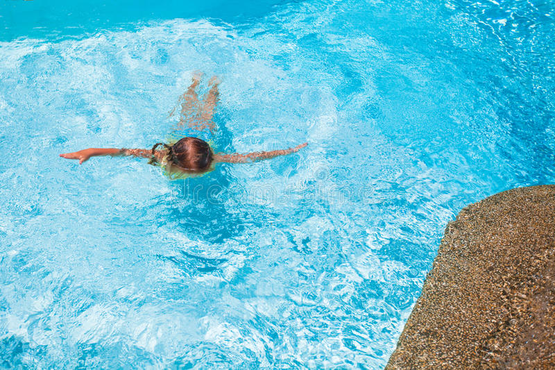 Little cute girl swims in the swimming pool at. Exotic resort. This image has attached release stock image
