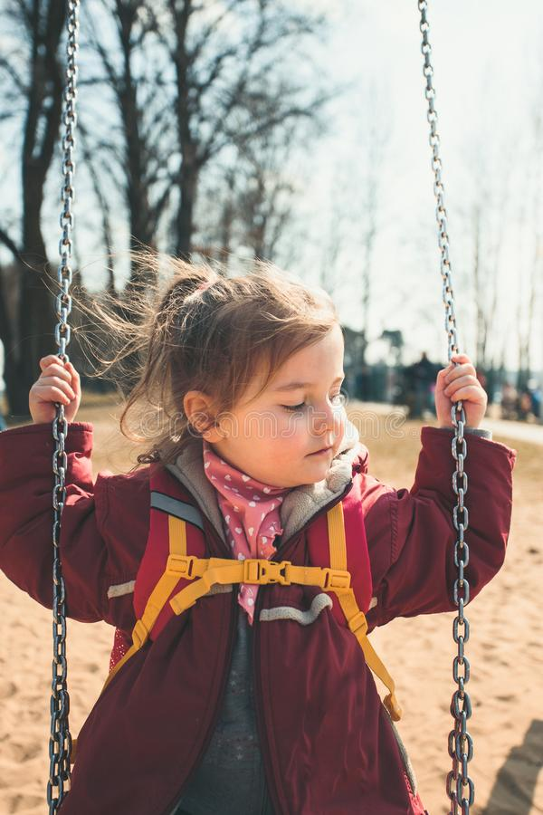 Little cute girl swinging in a park on sunny spring day stock photography