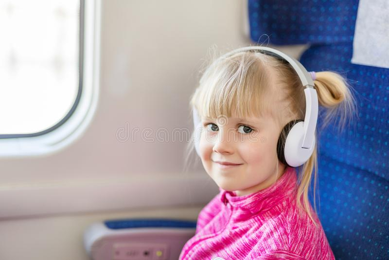 Little cute girl travelling by train. Kid listening to music with white headphones. Children activity and entertainment during. Trip concept royalty free stock image