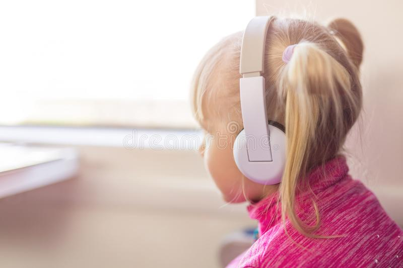 Little cute girl travelling by train. Kid listening to music with white headphones. Children activity and entertainment during tri. P concept royalty free stock image