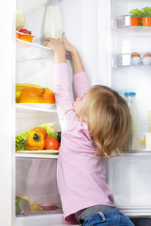 Little cute girl trying to pick food from fridge. Little cute girl trying to reach out and pick food from fridge. Vegetables and fruits in the refrigerator royalty free stock image