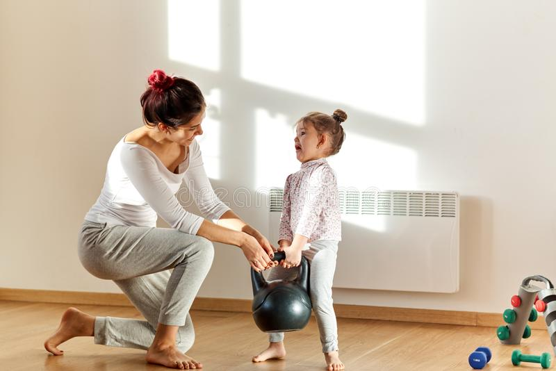 Little cute girl with work and fun expression of trying to lift a heavy weight. Her mom smiles at the funny picture and helps stock photo