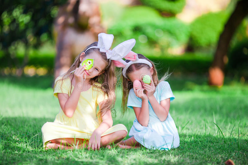 Little cute girls with bunny ears have fun with eggs on Easter holiday. Adorable girl wearing bunny ears holding basket with Easter eggs stock images