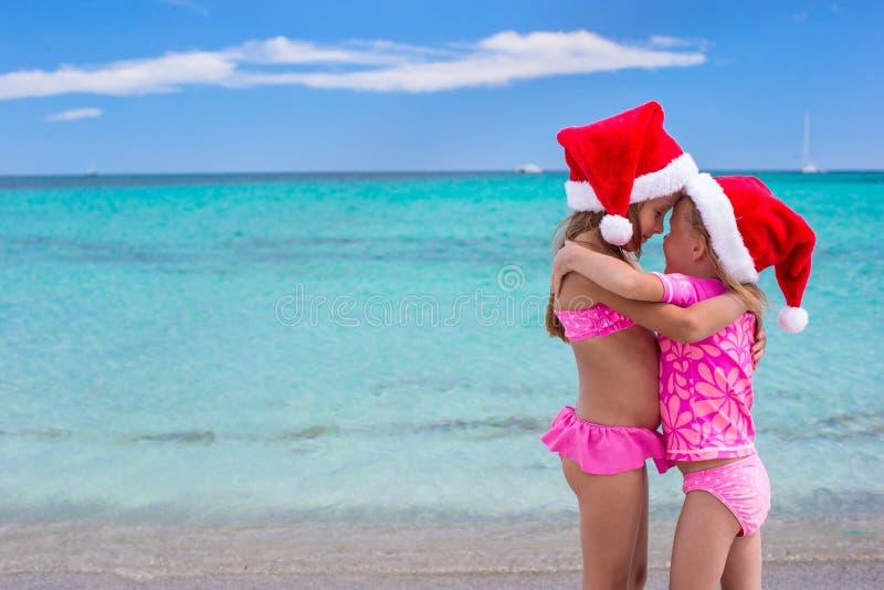 Little cute girls in Santa hats having fun on. Little cute girls in Christmas hats on the exotic beach stock photo