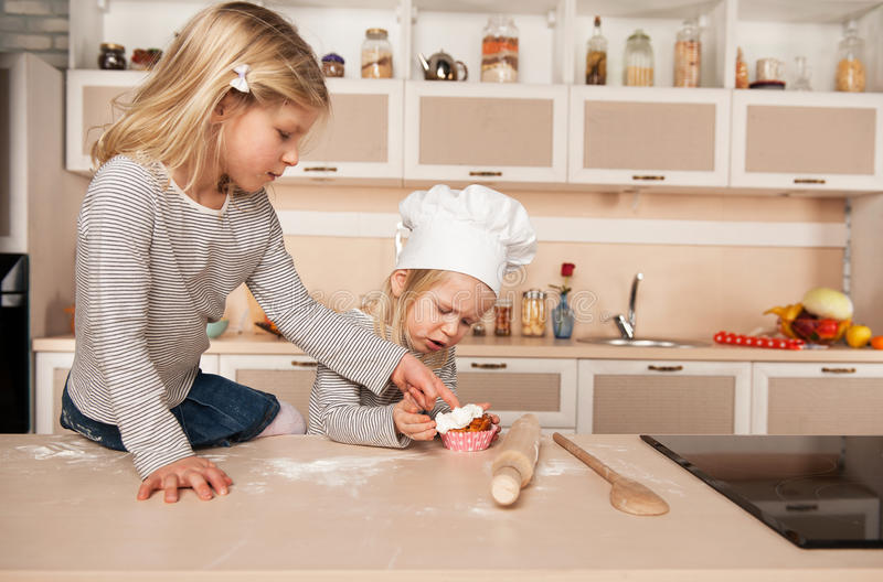 Little cute girls tasting cake in kitchen stock photo