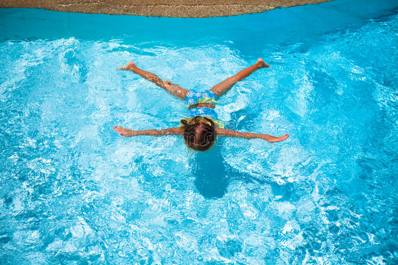 Little cute happy girl swims in the swimming pool. This image has attached release stock photo