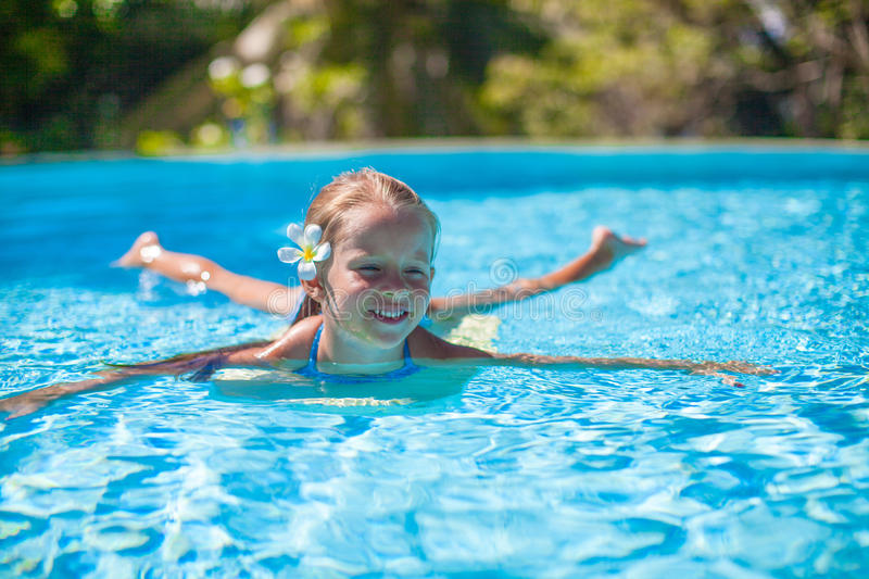 Attached Swimming Pool : Little cute happy girl swims in the swimming pool stock
