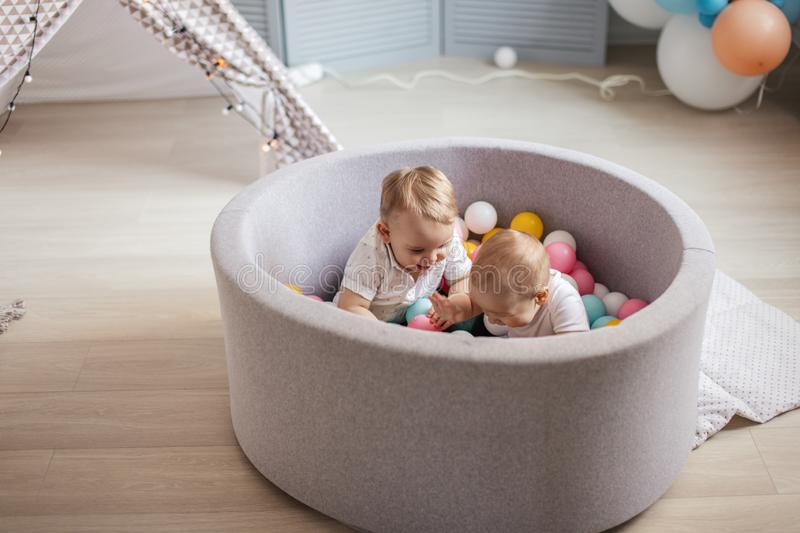 Little cute happy kids play with balls in ball pit in Play room. Birthday party. Two happy cute one year old infant boys are playing with colourful balls in a stock photography