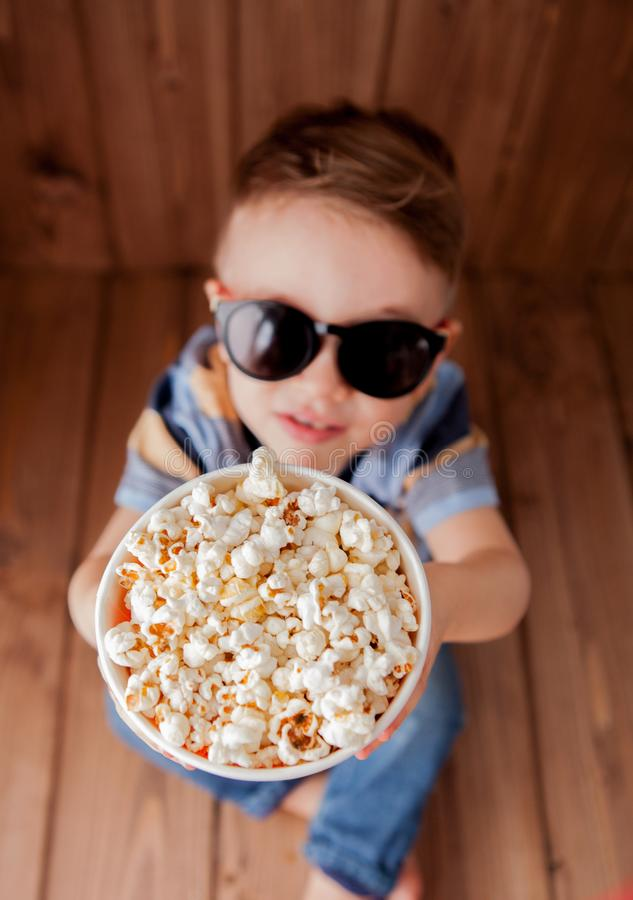Little cute kid baby boy 2-3 years old , 3d imax cinema glasses holding bucket for popcorn, eating fast food on wooden background royalty free stock photography