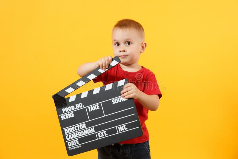 Little cute kid baby boy 3-4 years old in red t-shirt holding in hand classik black film making clapperboard looking royalty free stock image