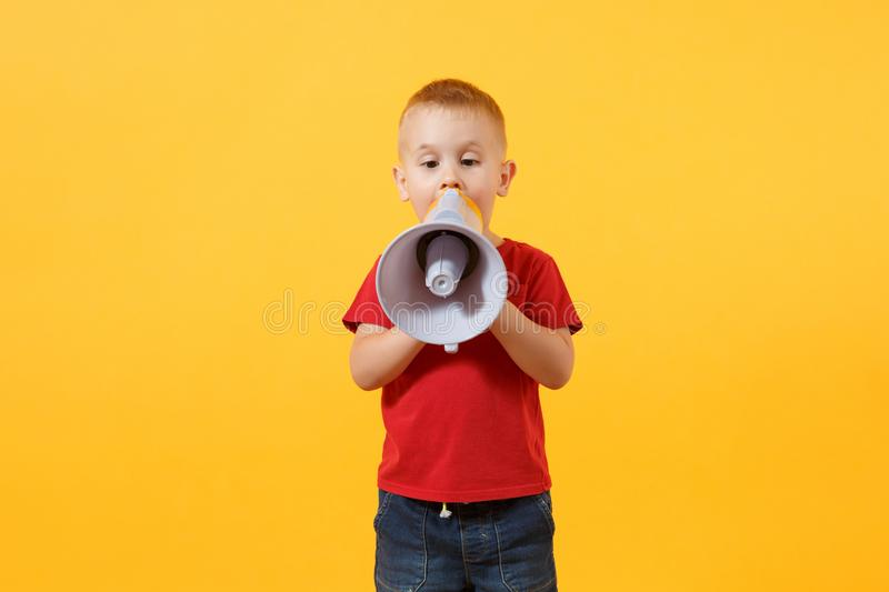 Little cute kid baby boy 3-4 years old in red t-shirt holding in hand, speaking in electronic gray megaphone, looking royalty free stock photos