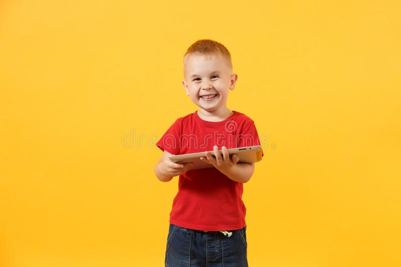 Little cute kid baby boy 3-4 years old in red t-shirt holding in hand tablet pc computer isolated on yellow background. Kids childhood lifestyle concept stock image