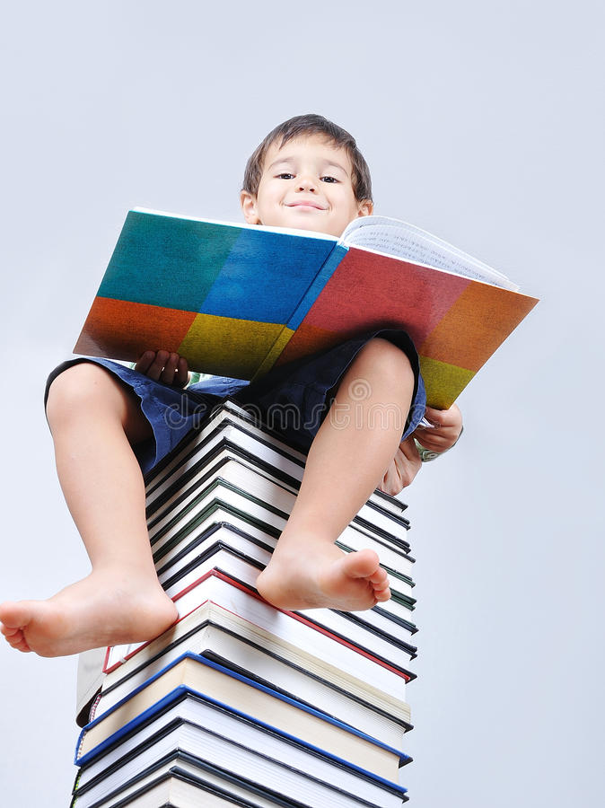 A little cute kid and books. A little cute kid and large number of books as a tower stock photo