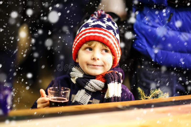 Little kid boy drinking hot chocolate on Christmas market. Little cute kid boy with cup of steaming hot chocolate or children punch. Happy child on Christmas stock photo