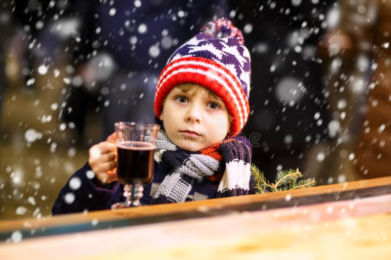 Little kid boy drinking hot chocolate on Christmas market. Little cute kid boy with cup of steaming hot chocolate or children punch. Happy child on Christmas royalty free stock image